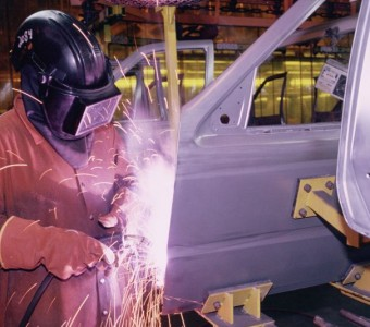 Custom Paint & Auto employee welding a door on a car in Charlotte NC