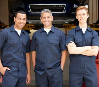 Three auto body repair specialists from Custom Paint & Body standing in front of the shop in Charlotte, NC