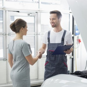 Smiling maintenance engineer shaking hands with female customer in collision repair shop